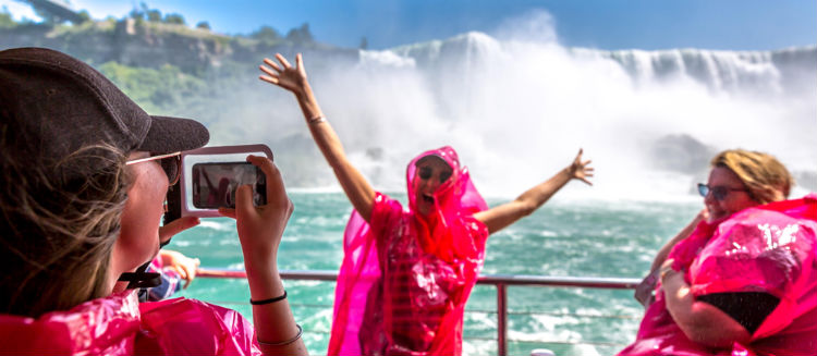 Three women on the Hornblower in Niagara Falls wearing pink ponchos.