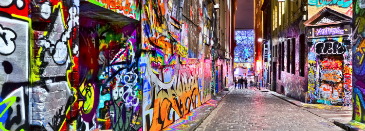 A street with walls covered in graffiti at night but well lit with street lamps