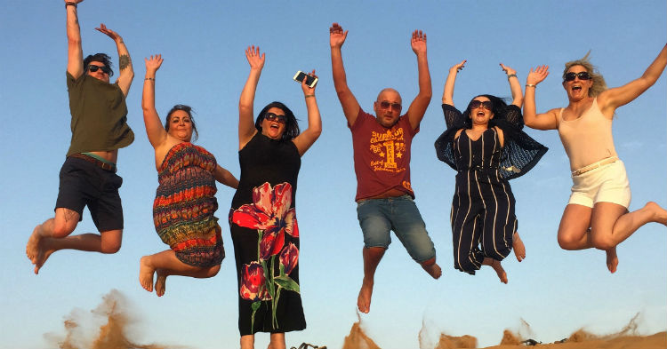 Six people jumping on the sand dunes in Dubai