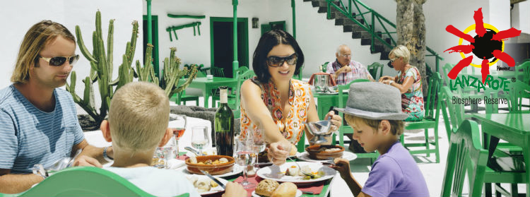 A family dining in Lanzarote, the building behind them in white and green.