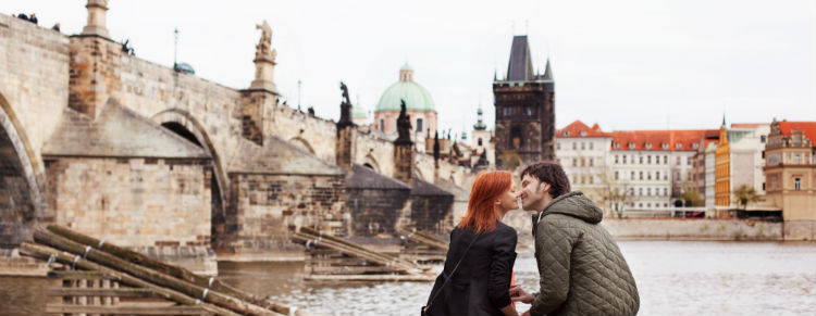 Couple kissing beside the Charles Bridge in Prague