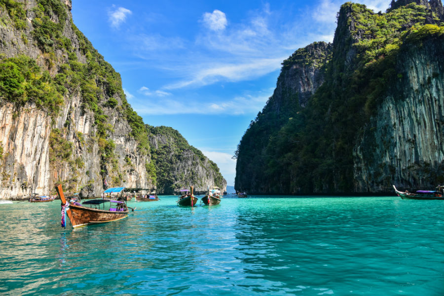 A rocky cove in thailand with boats