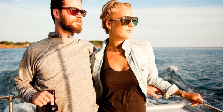 A male and female couple on a boat cruise at sunset around the Prince Edward Island coastline