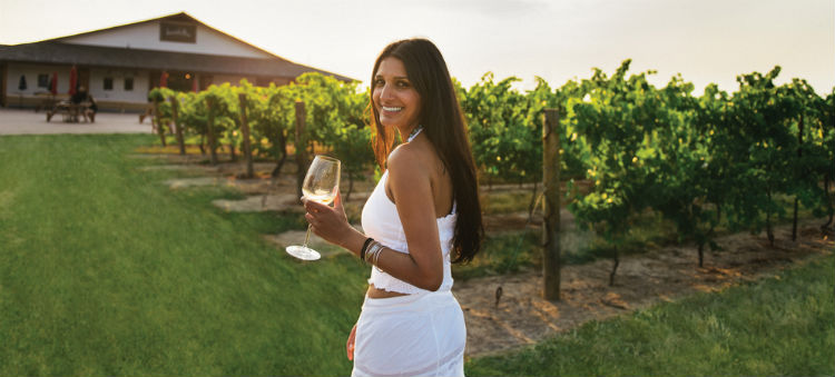 A woman with dark hair wearing a white outfit enjoying a wine on a vineyard in Niagara-on-the-Lake.