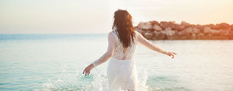 A bride running into the sea with the sun setting behind her