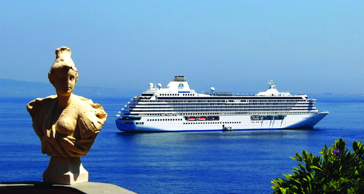 The Crystal Serenity behind see off in the distance with a statue seen in the foreground.