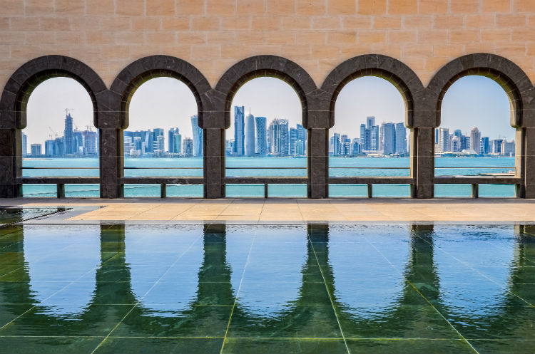 Arches in Doha with the modern skyline seen through the other side.
