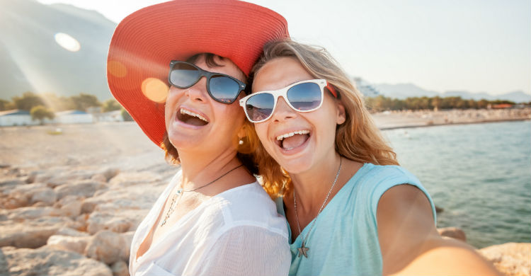 A mother and daughter looking at the camera with wide smiles. they are both weating sunglasses and you can see a beach in the background.