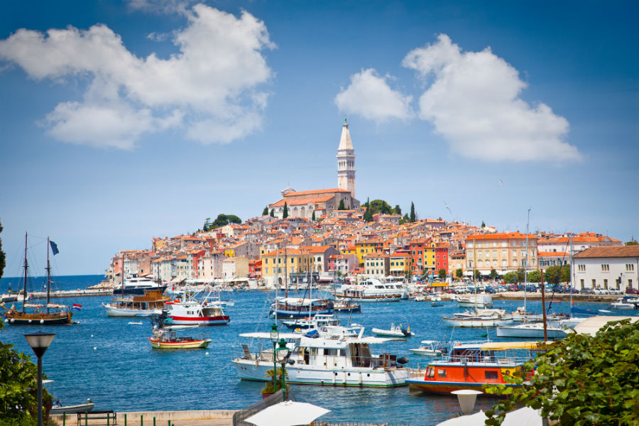 Old Istrian town in Rovinj Croatia during the day with lots of boats in the harbour.