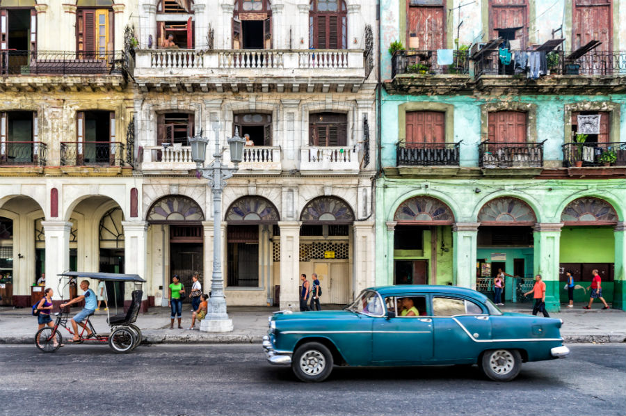 Buildings in Havana Cuba with a blue car outside them.