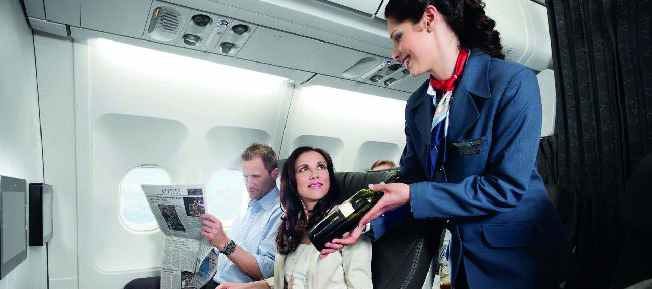 An Air Transat air hostess talking to two passengers who are eating their meals and she is presenting a bottle of wine.