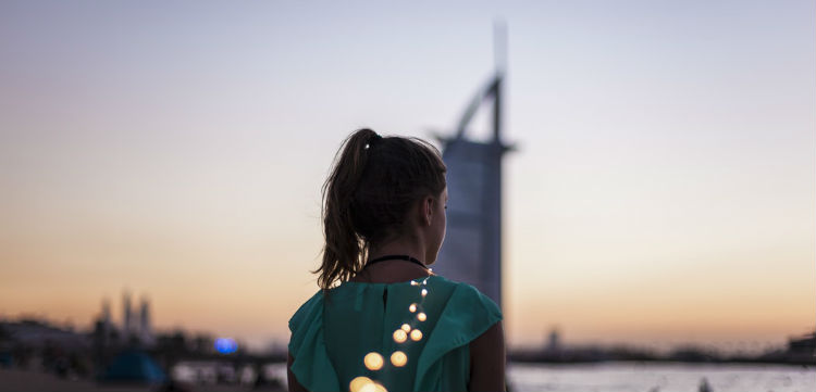 A girl with her back to the camera at sunset with the Burj Khalifa seen in the background.