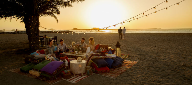 A group fo adult friends drinking and eating on a beach at sunset. There is a big palm tree directly behind them and another couple seen in the distance.