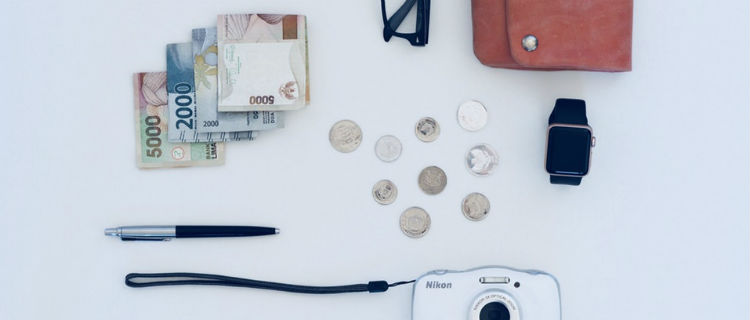 Money, a pen, coins, and a purse laid out on a white background.