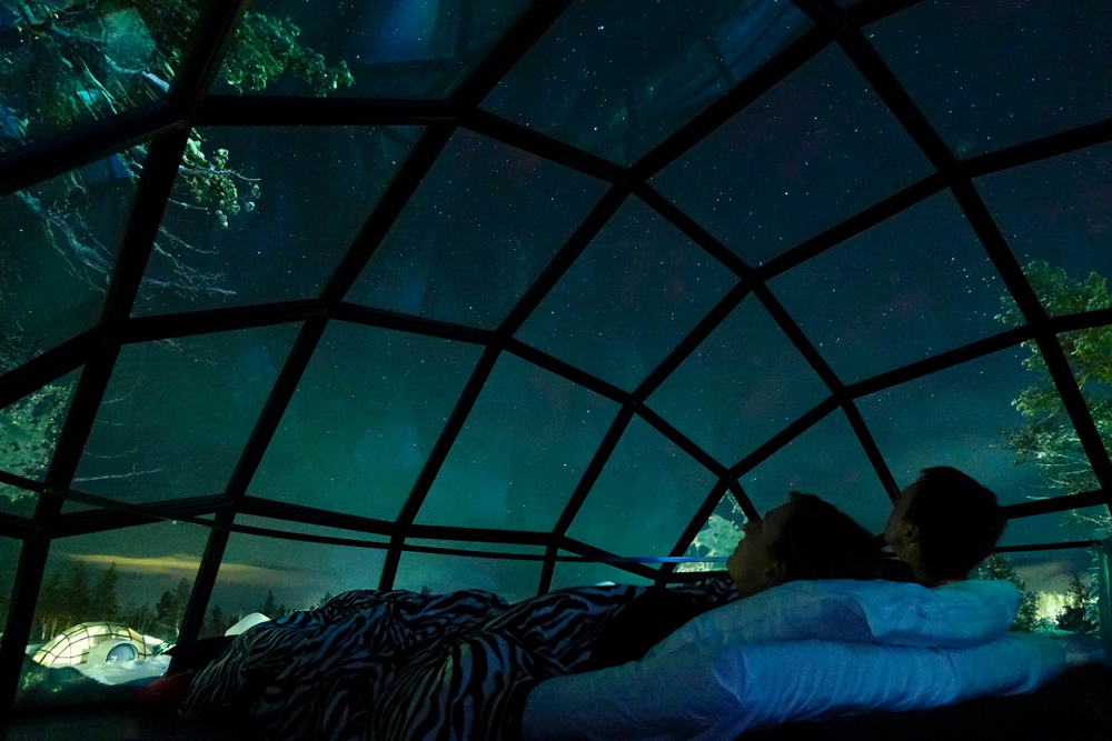 A couple lying back in bed looking up at the northern lights in Finland through a domed roof.