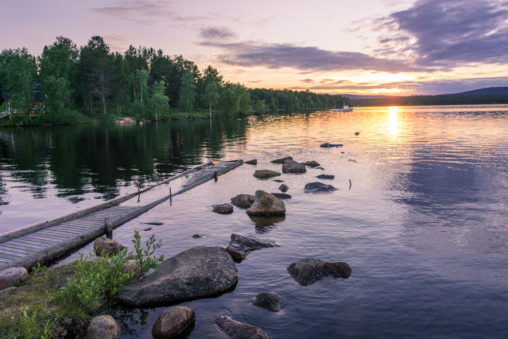 A lake in Finland with the midnight sun looking over it