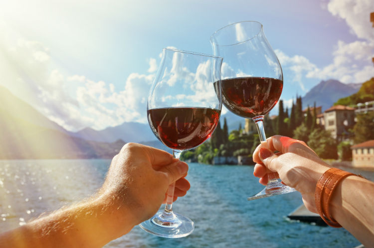 Two hands clinking wine glasses together (which are half full of red wine) with an Italian lake seen in the background.