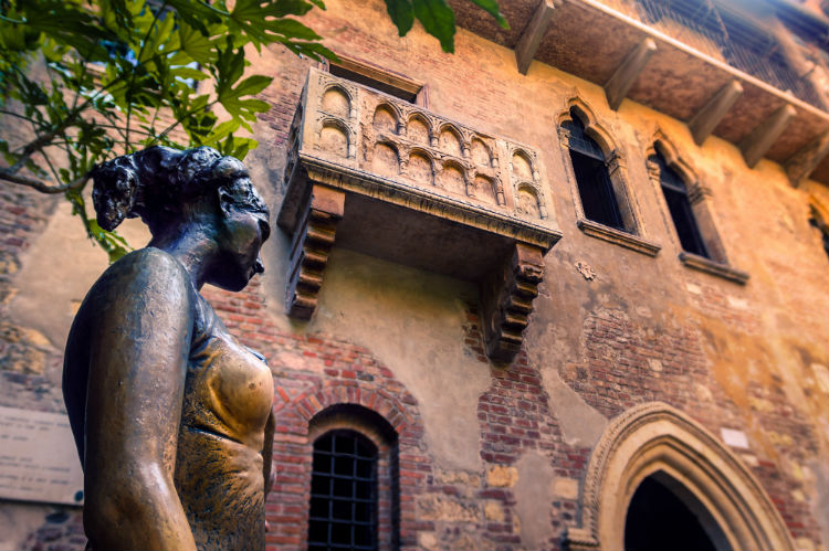 A statue of Juliet taken from a low angle with her balcony being seen up above.