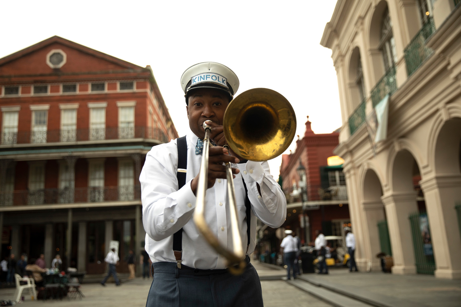A man with a trumpet looking directly into the camera on a New Orleans street.