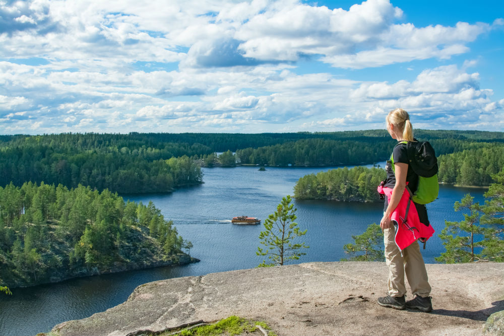 A woman standing on a rock overlooking a lake in Finland