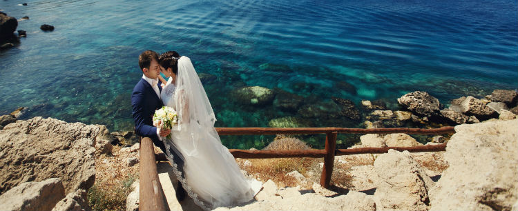 A newly married couple dressed in wedding attire skisisng on the rugged coastline of Cyprus