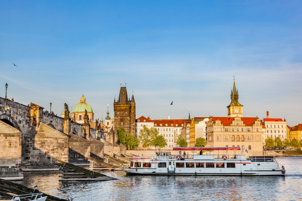 A river cruise along the Vltava river going under the Charles Bridge.