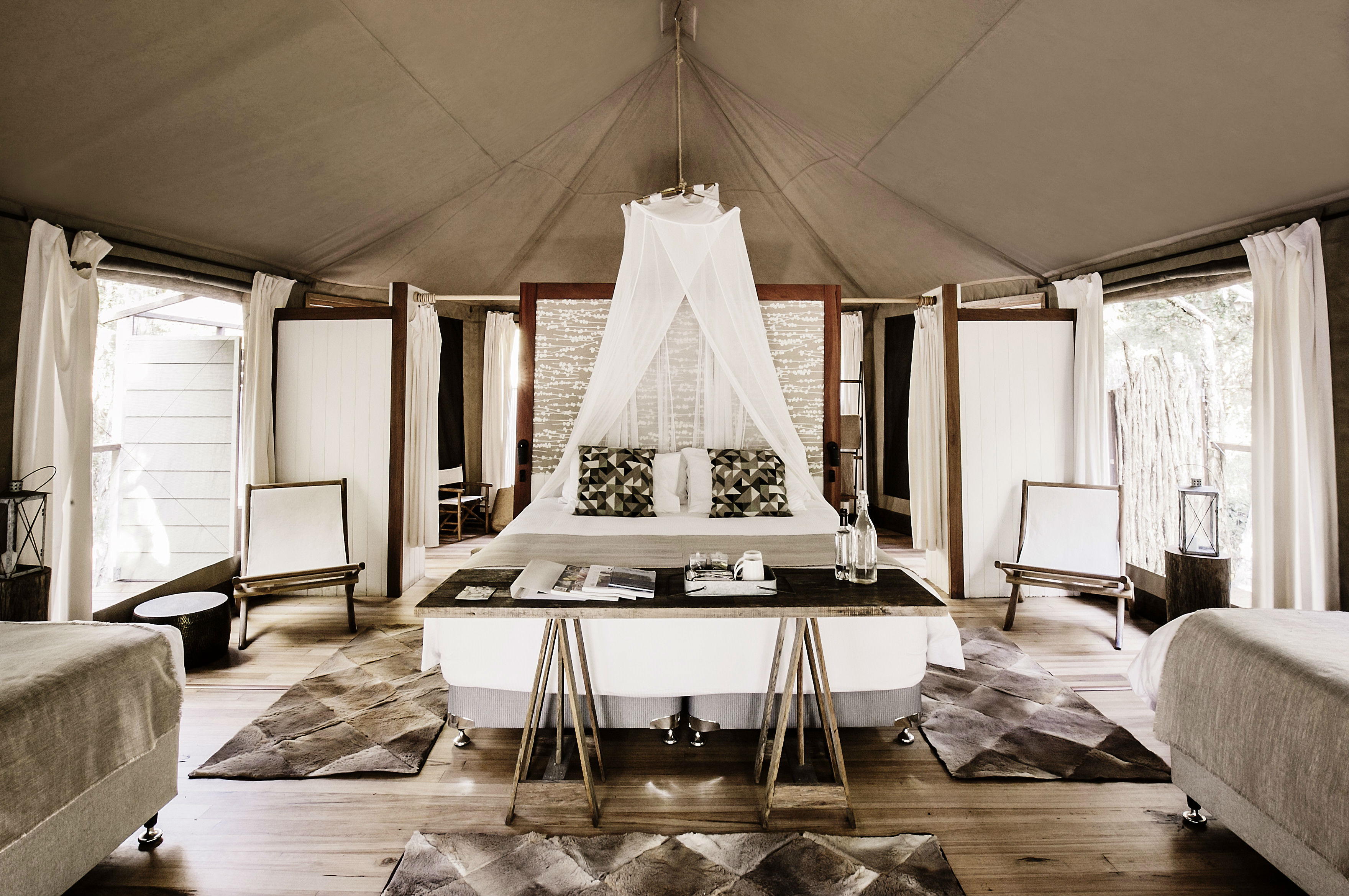 A luxury glamping text with white and light brown textiles.