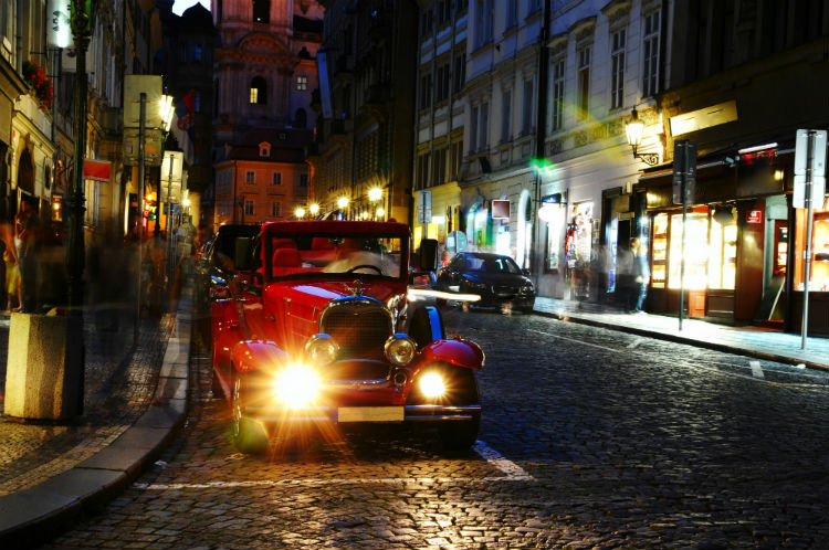 A vintage car in a Prague street at night time.