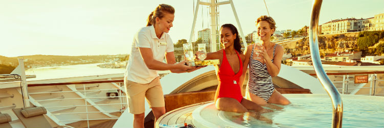 Two women being served drinks by a woman inm a whirlpool onboard a Seabourn ship. It is sunset.