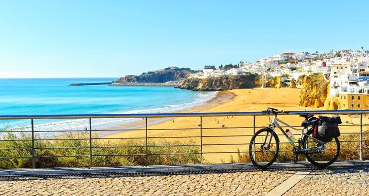 A sunny day on Algarve beach with a bike in the foreground.
