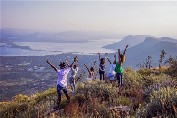 A group of people with their hands in the air up a mountain looking down on a city,