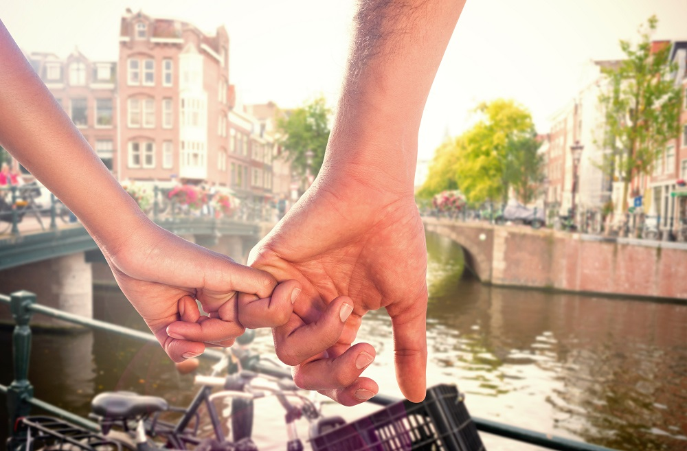 A picture of a couple holding pinkies in Amsterdam. They are in front of the canal