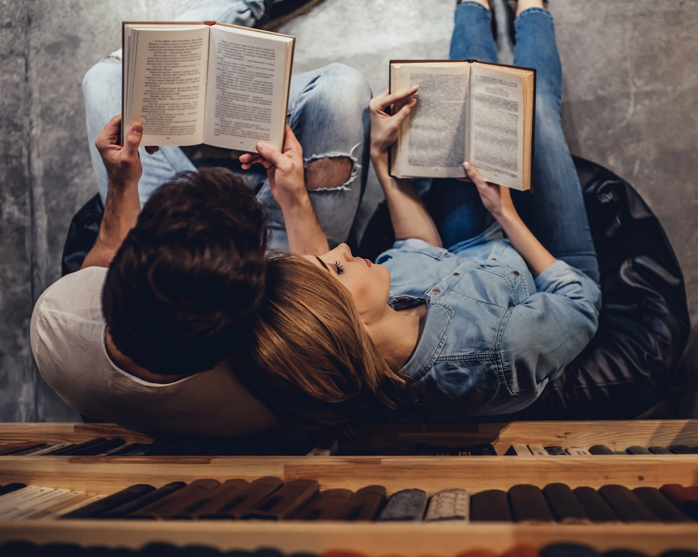 A picture of a couple reading books and leaning on each other