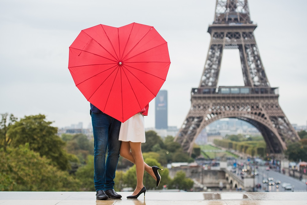 A picture of a couple in front of the Eiffel Tower. They are hidden by a heart-shaped umbrella